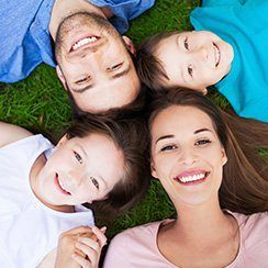 Mother father and two children laying on ground smiling at camera