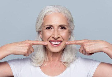 Senior woman pointing to her smile