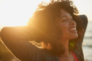 woman smiling in the sunset with porcelain veneers