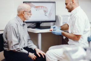 Dentist explaining why dental checkups with dentures matter.